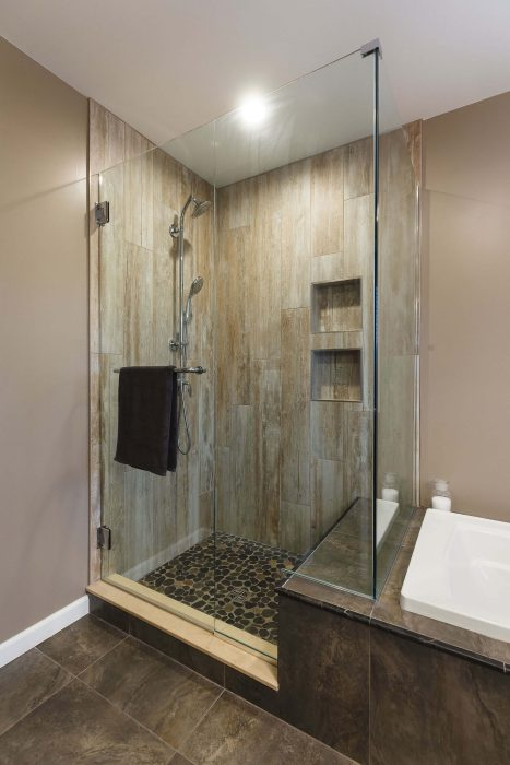 Walk In Shower With Dark Floors And Tile Accents