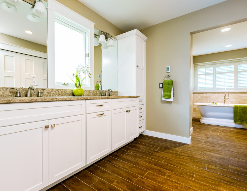 Master bathroom with white cabinets, wood looking tile, a cream countertop, and a white freestanding tub.